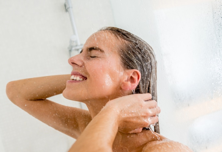 Happy woman taking a shower and relaxing
