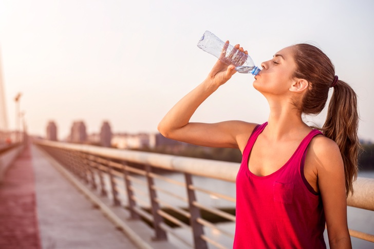 Young sportswoman with pony tail drinking water on the bridge while resting from morning jogging.