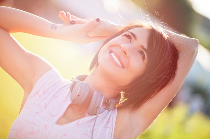 Portrait of a happy young woman with headphones around her neck outdoors