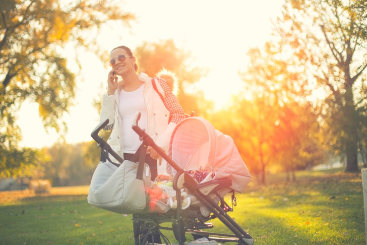 Busy babysitter talking on the phone outdoors,standing by baby stroller