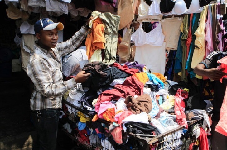 A vendor sells secondhand cloths at a stall in the busy Gikomba market in Nairobi September 18, 2014. Shaded by ragged squares of canvas, amid choking dust and the noise of hawkers, shoppers in Nairobi's Gikomba market can turn up Tommy Hilfiger jeans or a Burberry jacket for a fraction of the price in London's Regent Street or New York's Fifth Avenue. To match KENYA-TEXTILES/ Picture taken September 18, 2014 REUTERS/Noor Khamis (KENYA - Tags: BUSINESS TEXTILE)
