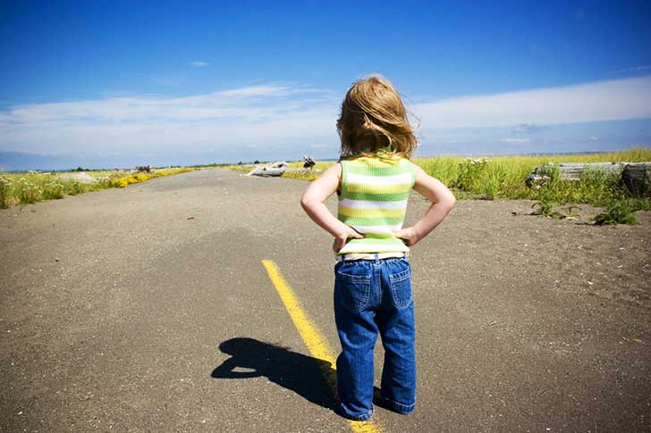 Determined-child-looking-down-road