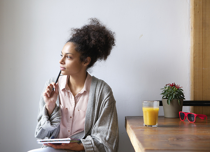 Young woman sitting at home with pen and paper